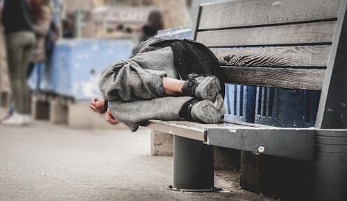 homeless person sleeping on bench